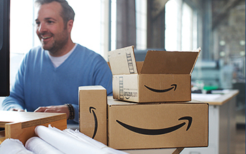 A smiling business owner on a computer surrounded by multiple Amazon cardboard shipping boxes.