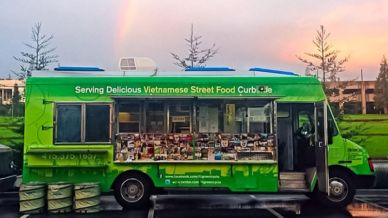 Green food truck serving delicious Vietnamese street food curbside.