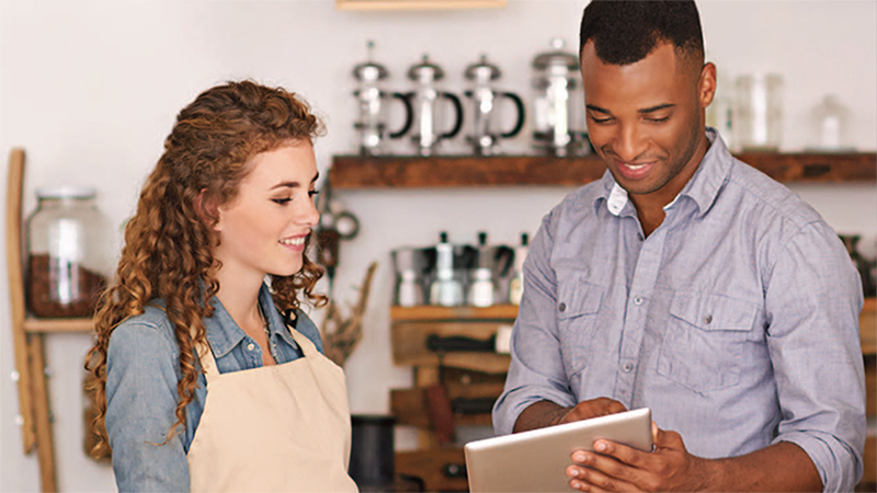 man showing tablet screen to woman