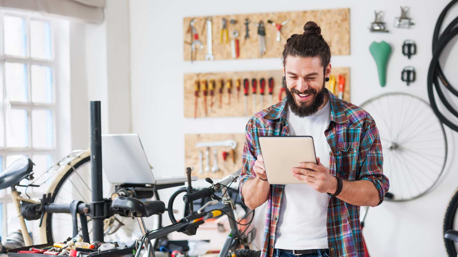 In a bike shop, a bearded young employee uses a tablet.