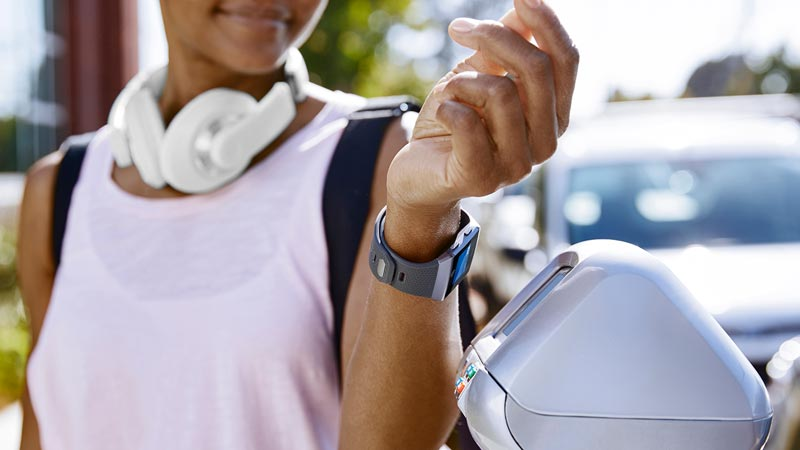 Closeup of woman using her smartwatch to pay the parking meter.