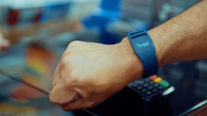 Close up of a person using a watch to pay, with the Trigg logo on the watch.
