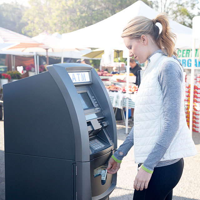 Lady getting cash from a standalone ATM at an outdoor market.