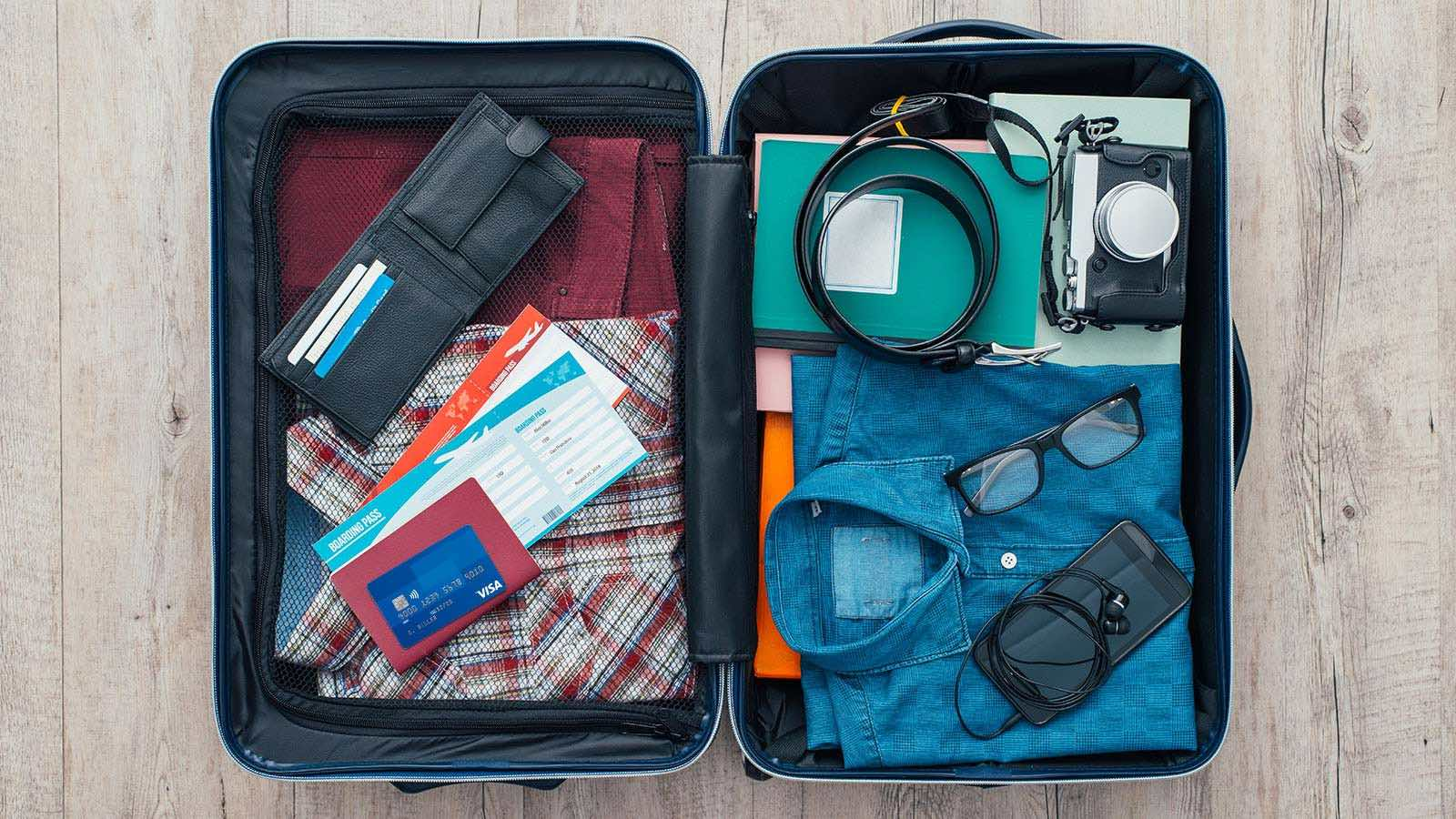 Open suitcase packed for travel with clothing, personal electronics, camera, wallet, airline tickets, passport and Visa card.