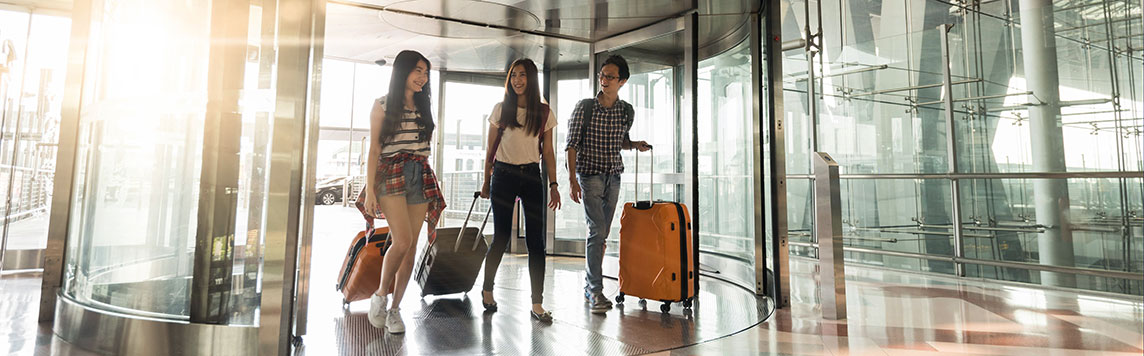 Two women and man with rolling suitcases entering fancy modern lobby.