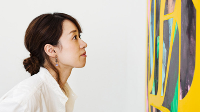 Woman standing in an art gallery, looking at an abstract modern painting