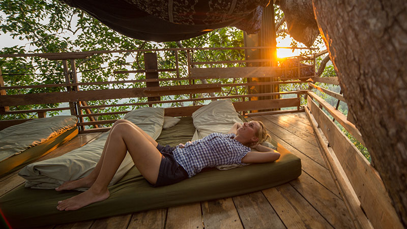 Woman relaxing in a tree house at sunset