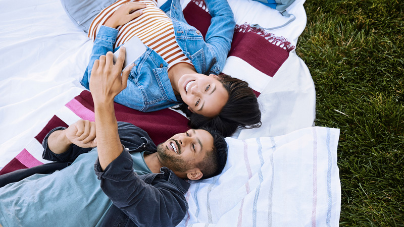 Couple on blanket on grass looking at mobile phone