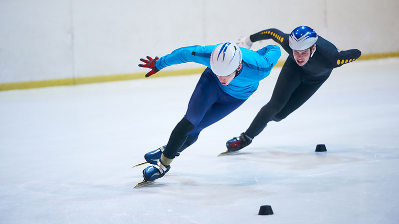 Two male Olympians make a tight turn on an ice skating rink.