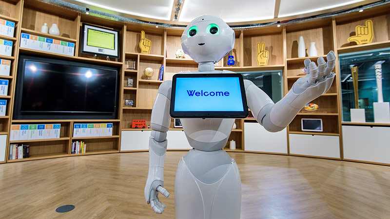 A semi-humanoid robot named Pepper standing with a tablet positioned just below its head with the message 'Welcome.'