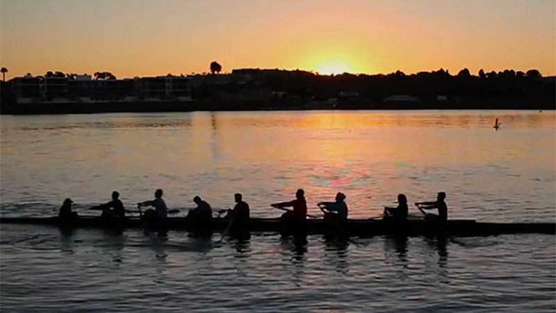 Team of Olympian rowers row on a lake against the backdrop of a sunset.