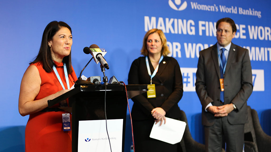 At a Women's World Banking event, a female speaker, makes an announcement at a podium.