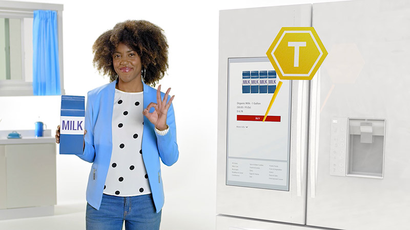 Happy shopper buying milk at a connected refrigerator