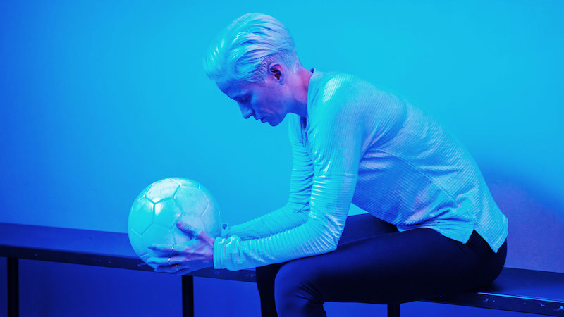 Megan Rapinoe holding a soccer ball while sitting on a bench.