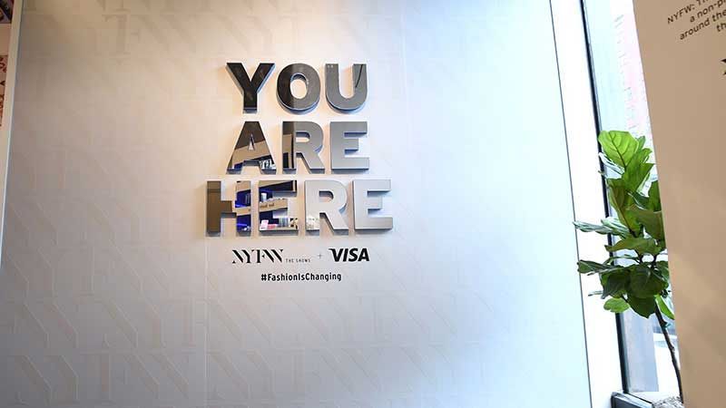 A pop up store wall features a graphic with the words 'You are here'.