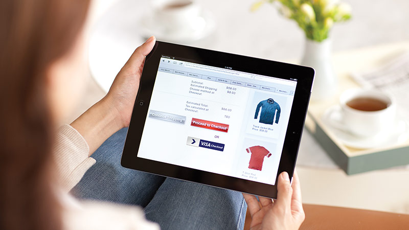 A woman holds a tablet, on the display is an online shopping cart with a Visa Checkout button.