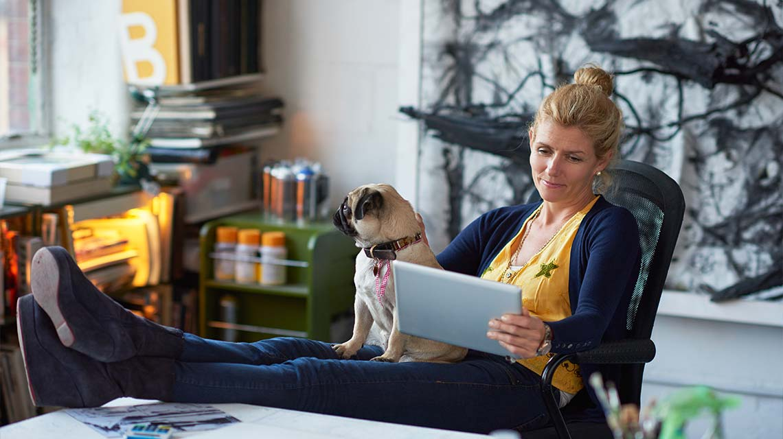 Woman kicking her feet up on a desk with a dog on her lap, and smiling at a tablet.