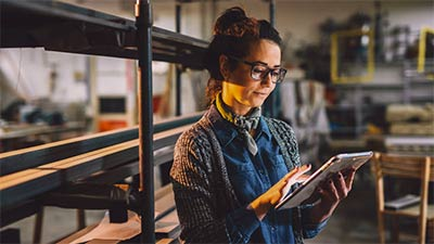 A woman wearing glasses using an iPad to review details about her business.