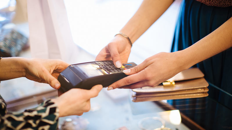 Female customer paying on credit card reader in boutique