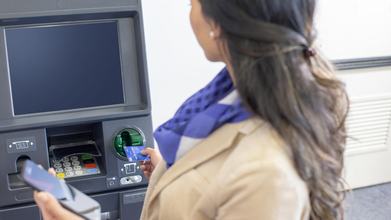 Woman inserting Visa card at an ATM.