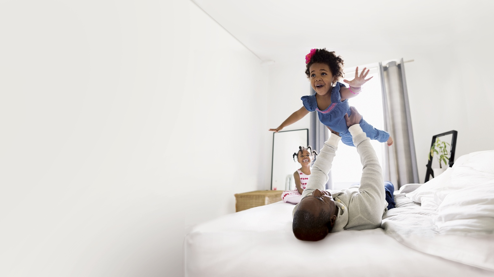 Father and daughter playing on the bed and smiling.