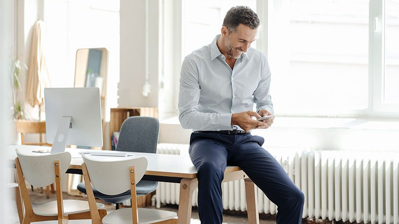 Man looking at his smartphone while sitting at the edge of his desk.