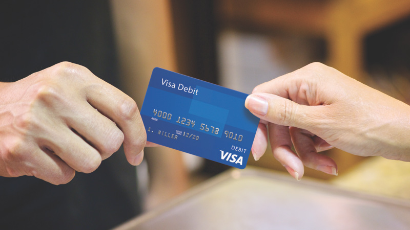 Customer handing over debit card for in-store purchase.