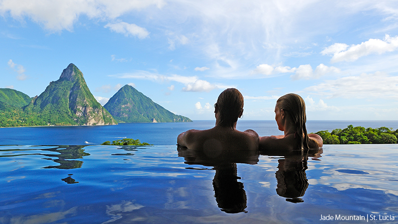 Couple sitting in affinity pool with beautiful mountains and water behind them at Jade Mountain, St. Lucia.
