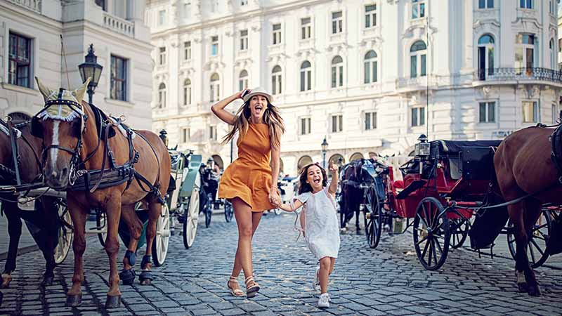 Happy woman and child walking among horses on a cobblestone street.