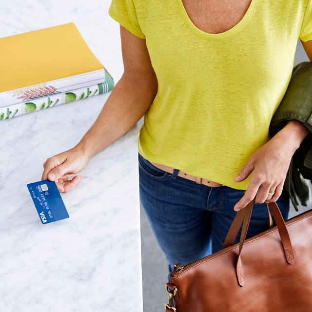 Closeup of woman in yellow shirt taking her contactless visa card as she leaves home