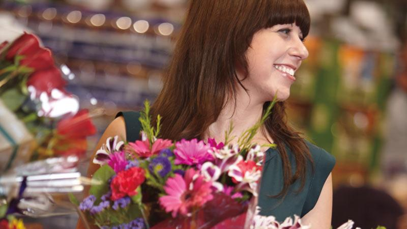 Young smiling woman holding bouquets of Costco flowers.