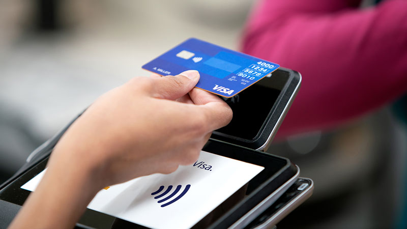 Close up of person using Tap to Pay at a terminal in a store.