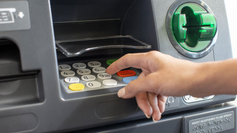 Closeup of a woman's hand at an ATM.