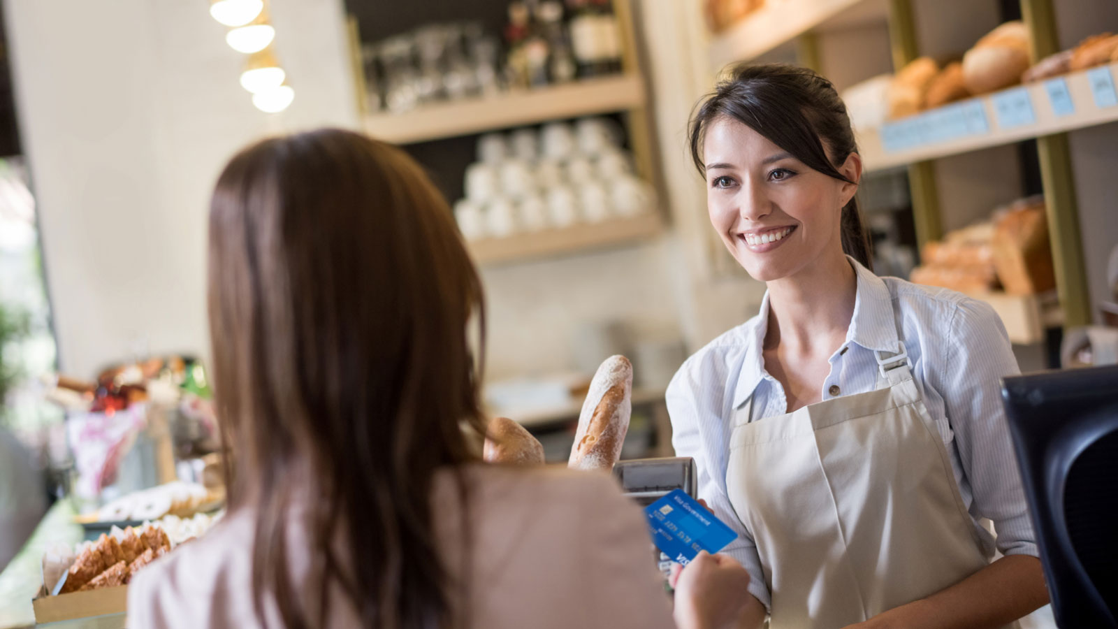 Woman paying with credit card at a bakery.