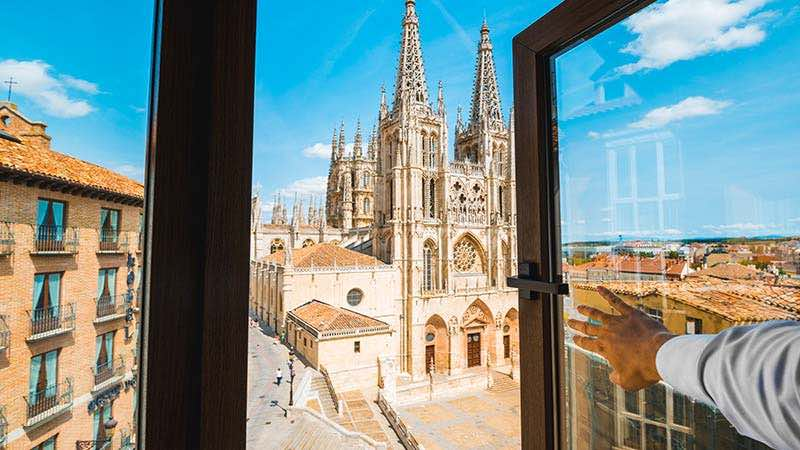 A man looks out his hotel room window towards a historic cathedral in Spain.