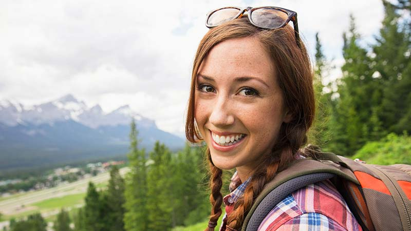 A happy backpacker, in a magnificent outdoor setting, smiles at the camera.