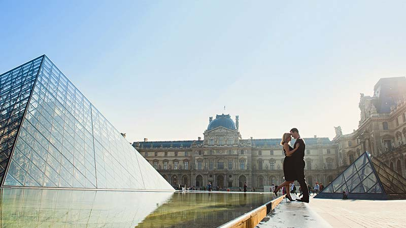 A romantic couple embrace outside of the Louvre museum in Paris.