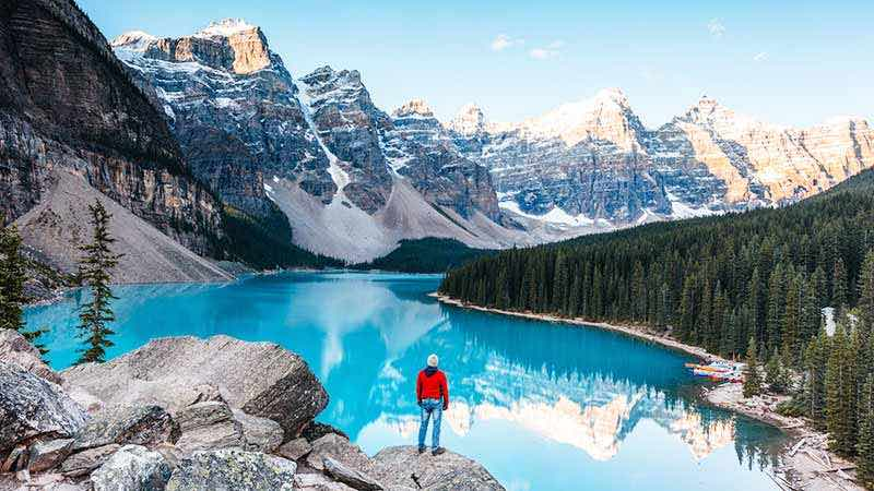Man standing on rock, looking at a lake and snow-capped mountains.
