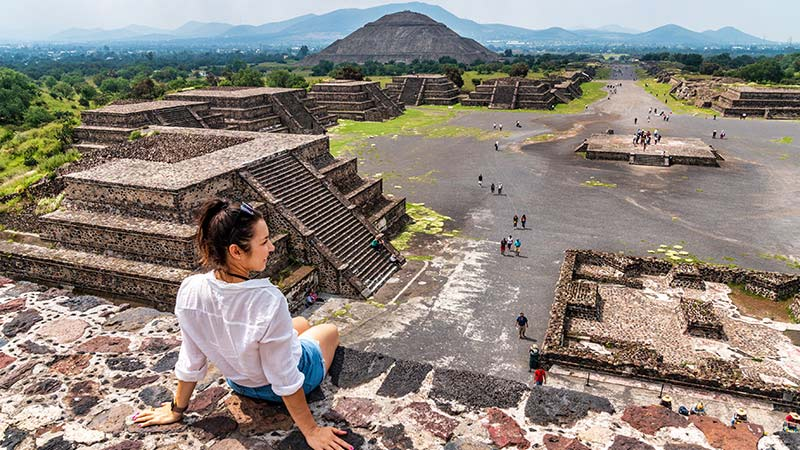 A young woman relaxes atop an ancient pyramid in Mexico.