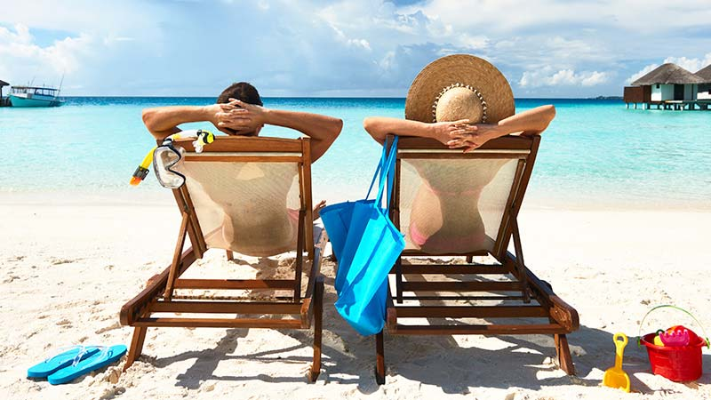 Man and woman relaxing on a beach.