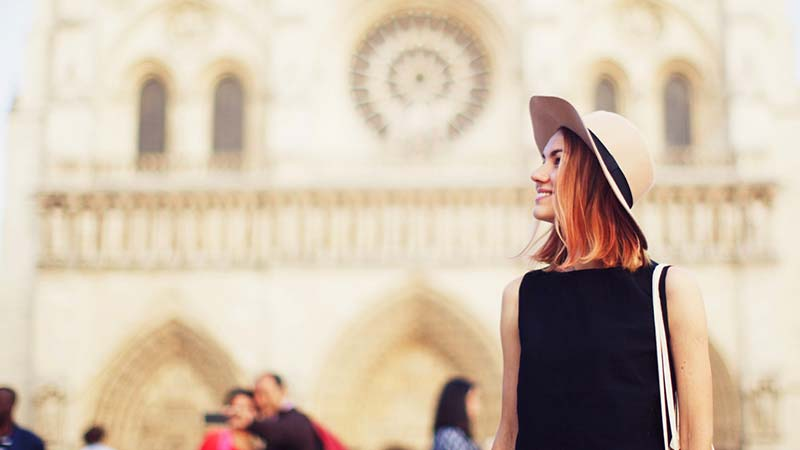 A stylish young woman stands in front of Notre Dame cathedral.
