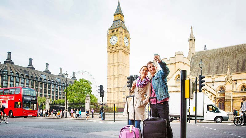 A young couple take a selfie in front of a historical building in London.