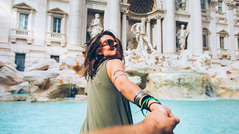 A smiling woman in front of Trevi Fountain in Rome, Italy.