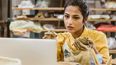 Female small business owner in pottery studio holding clay and looking at computer.