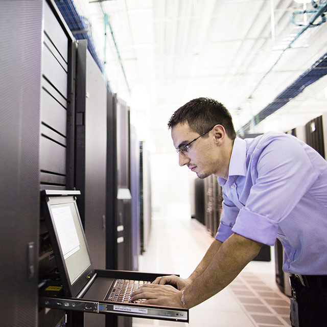 Man working on computer terminal in data center.